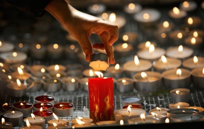 A-woman-lights-a-candle-during-a-special-service-for-the-victims-of-the-plane-crash-in-Smolensk-in-a-Catholic-Cathedral-in-Moscow-Sunday-April-11-2010.-AP-PhotoAlexander-Zemlianichenko-960x608